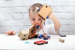 Little Boy examine les tractions de robot les fils, puce servo images libres de droits