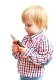 Little boy examines pliers. Stock Images