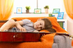 Little boy examining guitar on sofa Stock Image
