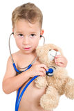 Little boy examining a teddy bear with a stethoscope Royalty Free Stock Image