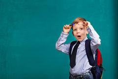 Little Boy in eyeglasses with big backpack. School, kid, rucksack. Cheerful smiling little boy opens his mouth in surprise. Looking at camera. School concept Stock Images