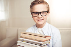 Little boy in eyeglasses holding pile of books and smiling at camera Stock Images