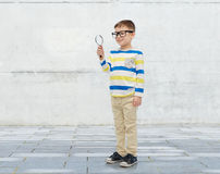Little boy in eyeglasses with magnifying glass. Childhood, education, investigation, discovery and people concept - happy little boy in eyeglasses with Stock Images