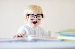 Little boy with eyeglasses reading book Royalty Free Stock Photography
