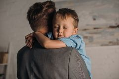 Little boy with eyes closed hugging father. At home royalty free stock photography