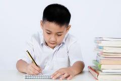 Little Boy för asiatisk kines bärande student Uniform Writting Homewo royaltyfri bild