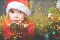 Little boy fairy blowing fairy magical glitter, stardust at Christmas. Christmas tree. Xmas child and New Year holiday. Merry Cristmas your family Stock Photos