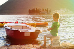 Little boy fastening boat at sunset on the sea Royalty Free Stock Photo