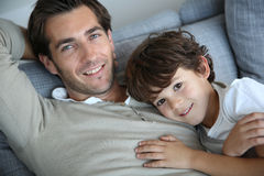 Little boy with father lying on sofa Royalty Free Stock Image