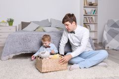 Little boy, father play with toys in basket on carpet Stock Image