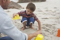 Little Boy And Father Playing With Sand royalty free stock photography