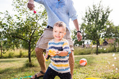 Little boy with father playing with water guns, splashing Stock Images