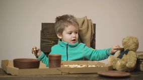 Little boy feed toy friend from spoon. Child have dinner with teddy bear friend. Eat right with a healthy bite. Cute. Child boy eats a pizza and feeds a toy stock video