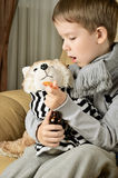 Little boy feeds medicinal syrup the toy dog and says AAA Royalty Free Stock Image