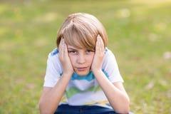 Little boy feeling sad in the park Royalty Free Stock Photo