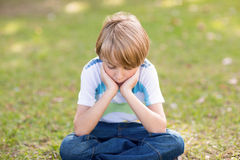 Little boy feeling sad in the park Stock Images
