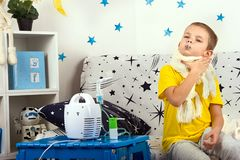 The little boy feels pain in the throat,measures the temperature. Child makes inhalation nebulizer Stock Images