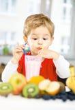 Little Boy felice che beve un frullato sano nella sua casa accogliente, w fotografia stock libera da diritti