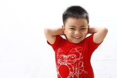Little Boy feliz que lleva a cabo la parte posterior de su cabeza Imagen de archivo