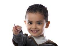 Little Boy feliz que señala con la pluma Imagen de archivo libre de regalías