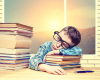 Little boy fells asleep over a stack of books Royalty Free Stock Images