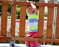 Little boy at the fence of playground stock photo
