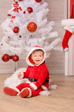 Little boy in festive attire at christmas tree Stock Images