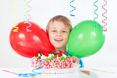 Little boy with a festive cake and balloons on white background Stock Image