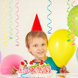 Little boy in festive cap with birthday cake and balloons Stock Images