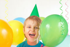 Little boy in festive cap with holiday balls and streamer Royalty Free Stock Images