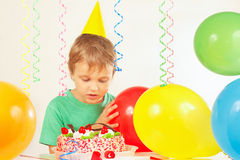 Little boy in festive cap looking at birthday cake Royalty Free Stock Photos