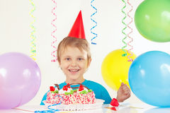 Little boy in festive hat with birthday cake and balloons Stock Photography