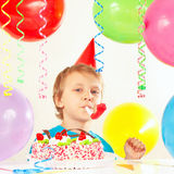 Little boy in festive hat with birthday cake with whistle and holiday balloons Stock Images
