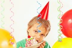 Little boy in festive hat eating birthday cake Royalty Free Stock Image
