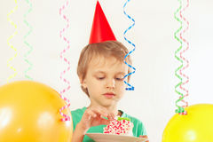 Little boy in festive hat eating piece of birthday cake Stock Photography