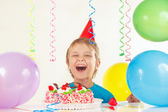 Little boy in festive hat with festive cake and balloons Royalty Free Stock Photos