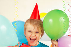 Little boy in festive hat with holiday balls and streamer Royalty Free Stock Photos