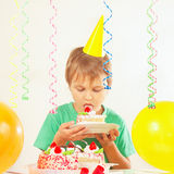 Little boy in festive hat tasting piece of birthday cake Stock Images