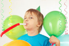Little boy in festive hat with whistle and holiday balloons and streamer Royalty Free Stock Images