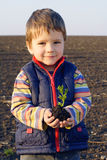 Little boy on field holding the plan Royalty Free Stock Image