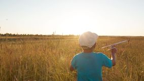 A little boy in field running toward with a toy plane stock video