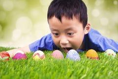 Little boy finding easter eggs on grass Stock Photo