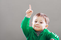 Little boy finger upward. Little boy with idea showing finger upward over grey backgound Royalty Free Stock Images