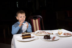 Little boy finishing off a slice of cake at table Royalty Free Stock Photography