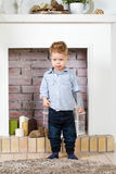 Little boy at a fireplace. Little boy costs at a fireplace Stock Images