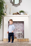 Little boy at a fireplace. Little boy costs at a fireplace Royalty Free Stock Image