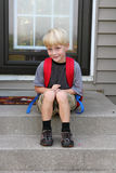 Little Boy First Day of School. A cute young child is sitting on his front steps of his home wearing his backback on his first day of school Stock Image