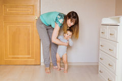 Little boy first steps with the help of mother. Little boy first steps with the help of mom stock photo