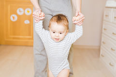 Little boy first steps with the help of mother. Little boy first steps with the help of mom stock image