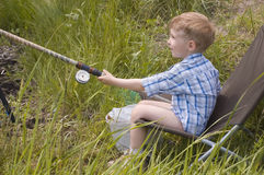 Little boy fishing stock photography
